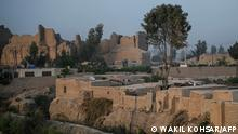 In this photograph taken on March 27, 2021, men walk along a pathway near an old palace were internally displaced families live, at the Qal-e-Kohna, a historic site in Lashkar Gah, the capital of Helmand Province. - Once the winter residence of sultans from illustrious Islamic dynasties, the ruins of a thousand-year-old royal city in southern Afghanistan has become home to hundreds of people who have fled Taliban clashes. (Photo by WAKIL KOHSAR / AFP) / TO GO WITH'Afghanistan-conflict-archeology-culture',FOCUS by Elise BLANCHARD and Rashid DURRANI