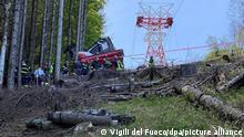 Die Aufnahme der Feuerwehr zeigt Feuerwehrleute an einer abgestürzten Gondel, die in einem Waldstück liegt. Bei dem Seilbahnunglück in der norditalienischen Provinz Verbano-Cusio-Ossola sind neun Menschen ums Leben gekommen, weitere wurden verletzt. +++ dpa-Bildfunk +++