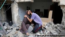 A Palestinian woman is kissed by her son after returning to their destroyed house following Israel- Hamas truce, in Beit Hanoun in the northern Gaza Strip, May 21, 2021. REUTERS/Mohammed Salem