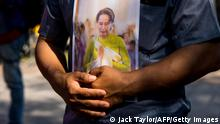 FILE PHOTO - A protester holds an image of Aung San Suu Kyi outside the United Nations building in Bangkok on February 3, 2021, during a demonstration against the military coup in Myanmar which saw civilian leader Suu Kyi being detained. (Photo by Jack TAYLOR / AFP) (Photo by JACK TAYLOR/AFP via Getty Images)