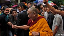 Tibetan spiritual leader the Dalai Lama is greeted by people as he walks to watch an exhibition of traditional Tibetan paintings in Dharmsala, India, Tuesday, July 6, 2010. The Dalai Lama turned 75 on Tuesday and he joined hundreds of cheering followers in this northern Indian town where he has been living in exile since he fled China in 1959. (AP Photo/Ashwini Bhatia)