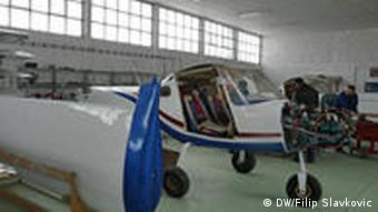 Airplane parts stand in a hangar