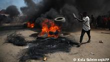 """*** Dieses Bild ist fertig zugeschnitten als Social Media Snack (für Facebook, Twitter, Instagram) im Tableau zu finden: Fach """"Images"""" —> Weltspiegel/Bilder des Tages *** A man throws a tyre a bonfire on the Kaduna-Abuja highway in Gauruka, near Abuja, Nigeria, on May 24, 2021 during a protest against incessant kidnapping and killing after gunmen kidnapped 16 residents and killed three others in Niger State. (Photo by Kola Sulaimon / AFP)"""