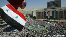 (FILES) In this file photo taken on May 24, 2007, Syrians gather in the capital Damascus during President Bashar al-Assad's campaign for a no-contest referendum. - President Bashar al-Assad, whose family has ruled Syria for over half a century, faces an election this week meant to cement his image as the only hope for recovery in the war-battered country, analysts say. (Photo by Louai Beshara / AFP)