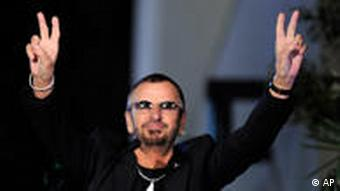 Ringo Starr gestures to the crowd during a ceremony to award him the 2,401st star on the Hollywood Walk of Fame in Los Angeles, Monday, Feb. 8, 2010. (AP Photo/Chris Pizzello)