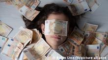 50-Euro-Noten auf dem Gesicht einer jungen Person