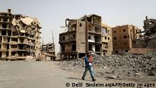 A picture taken on October 15, 2018, shows a man carrying his baby past piles of debris and damaged buildings in the northern Syrian city of Raqa. - The fighting ended on October 17 last year, when the city finally fell to the Syrian Democratic Forces, which then handed it over to the Raqa Civil Council (RCC) to govern. Rights group Amnesty International estimates around 80 percent of Raqa was devastated by fighting, including vital infrastructure like schools and hospitals. (Photo by Delil SOULEIMAN / AFP) (Photo credit should read DELIL SOULEIMAN/AFP via Getty Images)