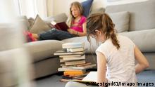 Two girls sitting in the living room reading books model released Symbolfoto property released PUBLICATIONxINxGERxSUIxAUTxHUNxONLY NEKF00041