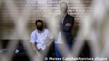 The sons of former Panamanian President Ricardo Martinelli, Ricardo Martinelli Linares, right, and his brother Luis Enrique wait inside a cell at the judicial court building in Guatemala City, Tuesday, July 7, 2020. The brothers were detained Monday on an international warrant from Interpol on charges of conspiracy to commit money laundering. (AP Photo/Moises Castillo)