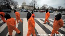 Demonstrators representing prisoners at the US Guantanamo Bay Naval Base walk during a rally against torture sponsored by Witness Against Torture with Amnesty International and the National Religious Campaign Against Torture 11 January 2008 on the National Mall in Washington, DC. AFP PHOTO / TIM SLOAN (Photo by Tim SLOAN / AFP) (Photo by TIM SLOAN/AFP via Getty Images)