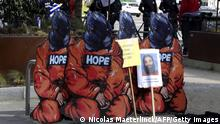 Four activists of Amnesty International disguised in Guantanamo hooded prisoners stage a protest ahead of a visit by US President Barack Obama to Belgium on March 25, 2014, in Brussels. AFP PHOTO / NICOLAS MAETERLINCK (Photo credit should read NICOLAS MAETERLINCK/AFP via Getty Images)