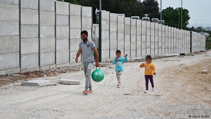 Zid pored kojeg prolazi muškarac s dvoje djece