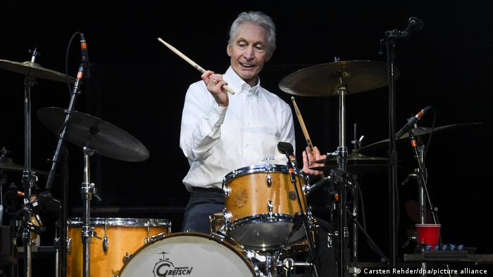 Charlie Watts drumming in a white shirt