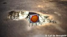 A Shell petrol station logo is refelected in a puddle in London, on Februrary 4, 2010. Royal Dutch Shell plans to axe 1,000 more jobs and sell some of its assets owing to an uncertain outlook and after annual profits plunged, the British energy giant said on Thursday. Net profit tumbled 52 percent to 12.52 billion dollars (9.0 billion euros) last year compared with 26.28 billion dollars in 2008, Shell said in an earnings statement. AFP PHOTO/CARL DE SOUZA (Photo by CARL DE SOUZA / AFP)