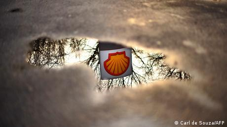A Shell petrol station logo is refelected in a puddle
