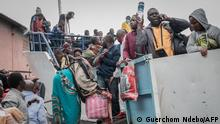 Goma residents are seen boarding a ferry after an evacuation order has been given on May 27, 2021. - The authorities in Goma, in the east of the Democratic Republic of Congo (DRC), on Thursday morning ordered the evacuation of part of the city because of the risk of eruption of the Nyiragongo volcano, immediately causing the exodus of tens of thousands of people. (Photo by Guerchom NDEBO / AFP)