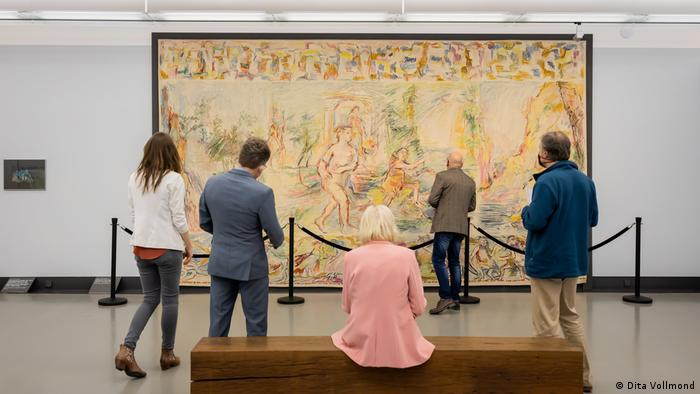 Museumgoers looking at a large tapestry.