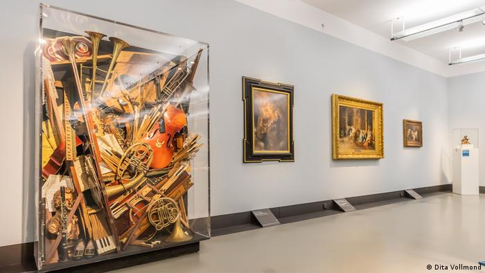 Various instruments, sheet music, a bust and other objects are mixed together behind a plexiglas screen.