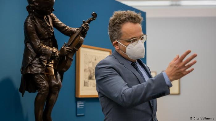 Damian Dombrowski standing in front of a bronze depiction of Mozart and holding up his hand.