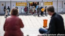 Menschen stehen am Schlossplatz vor einem Testzentrum an. Restaurants, Hotels und der Einzelhandel dürfen wieder aufmachen - Besucher müssen geimpft oder genesen sein oder einen negativen Test vorlegen. +++ dpa-Bildfunk +++