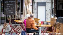 """""""Wir freuen uns auf euch - euer Carls Team"""" steht auf einer Tafel geschrieben, während Gäste daneben sitzen und in der Sonne ein Bier genießen. Restaurants, Hotels und der Einzelhandel dürfen wieder aufmachen - Besucher müssen geimpft oder genesen sein oder einen negativen Test vorlegen. +++ dpa-Bildfunk +++"""