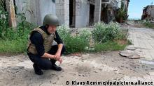 Robert Habeck, Bundesvorsitzender von Bündnis 90/Die Grünen, hockt auf dem Boden und betrachtet Munitionsreste in dem zerstörten, und seit 2015 verlassenen, Dorf unweit von Mariupol. (zu dpa «Habeck für Waffenlieferungen zur Selbstverteidigung an die Ukraine») +++ dpa-Bildfunk +++