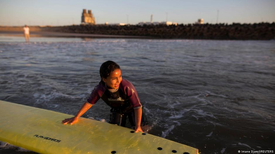 A young kid standing in the sea holding on to a surfboard