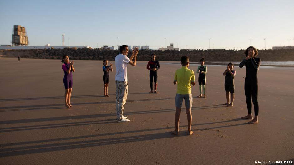 Surf coaches warming up with kids on the beach