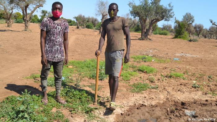 Two men standing in a field in Angola affected by drought