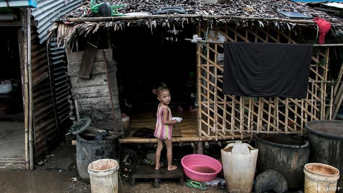 Ein Mädchen steht vor einer ärmlichen Bambushütte in einem Vorort von Yangon