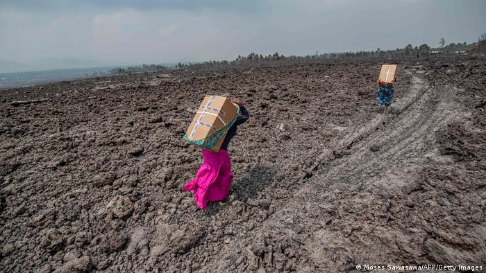 Residents wearing bright dresses carry goods on their backs, bent forward in field of ash