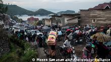 Residents flee Goma, Congo Thursday, May 27, 2021 , five days after Mount Nyiragongo erupted . A new eruption could occur at any moment, the military governor of Congo's North Kivu province, Lt. Gen. Constat Ndima Kongba, announced early Thursday. He ordered the evacuation of 10 of the 18 neighborhoods in the city of 2 million people. The center of Goma, which was spared when the volcano erupted last week, is now under threat, with activity being reported near the urban area and Lake Kivu, Kongba said. (AP Photo/Moses Sawasawa)