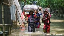 Bangladeshi women carry their belongings as they wade through flood waters following heavy mosoon rains in Kurigram on July 17, 2019. - In flood-prone Bangladesh, which is criss-crossed by rivers, around one-third of the country is underwater and people were being killed by lightning strikes, officials said (Photo by REHMAN ASAD / AFP)