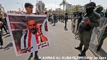 Iraqi security forces deploy during a demonstration in Tahrir Square in Baghdad on May 25, 2021, to demand accountability for a recent wave of killings targeting activists. The placard depicts renowned anti-government activist Ihab al-Wazni (Ehab al-Ouazni), who was shot dead in an ambush earlier this month. - Thousands of Iraqis demonstrated in the capital to demand justice over a wave of deadly attacks on pro-democracy activists and journalists. Waving portraits of victims, gunned down with silencers by unknown assailants, protesters converged on the capital's main squares including Tahrir, as police were deployed in force. (Photo by Ahmad AL-RUBAYE / AFP) (Photo by AHMAD AL-RUBAYE/AFP via Getty Images)