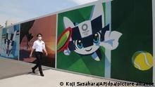 Ein Mann mit Mund-Nasen-Schutz geht an Plakaten vorbei, die für die Olympischen Spiele werben. Am 23. Juli, sollen in der Hauptstadt Tokio die Olympischen Spiele beginnen. +++ dpa-Bildfunk +++