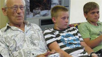 Christoph Janisch sits on a couch playing video games with his grandson and his grandson's friend