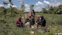 A group of migrants rest in a field near the Serbian village Majdan, close to the Hungary and Romania borders, on May 21, 2021. - Inside an abandoned house, onions sizzle as mother-of-four Seror struggles to cook an Iraqi speciality over an open fire, trying to maintain an illusion of home for her loved ones. The Alhayani family are among hundreds of people from the Middle East, Africa and Asia sheltering in derelict houses in Serbian villages close to the Hungary and Romania borders. Most are trying to get to Western Europe via Romania, a new hotspot on the Balkan migrant route where arrival numbers have been rising rapidly in the past two years. (Photo by OLIVER BUNIC / AFP)