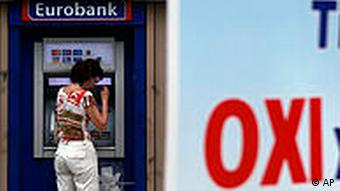 A woman takes out money from an ATM, as a banner announcing Thursday's general strike reads ''NO'', in central Athens, Wednesday, July 7, 2010. Greek unions are planning a general strike and protests against the draft law on Thursday. (AP Photo/Evi Zoupanou)