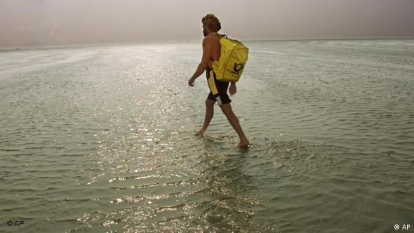 Ein Mann geht durch knöcheltiefes Wasser. Auf seinem Rücken trägt er einen gelben Rucksack der Deutschen Post