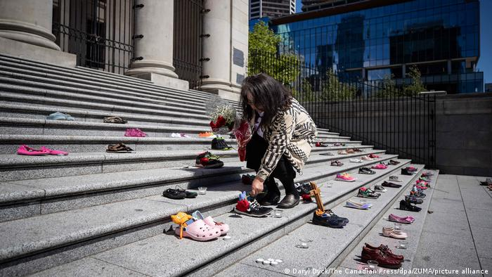 Delhia Nahanee lays roses on the steps of the Vancouver Art Gallery