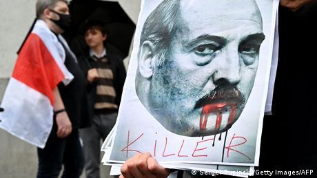 An activist, a member of the Belarusian diaspora in Ukraine, holds a placard depicting Belarusian President Alexander Lukashenko