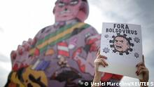 A demonstrator holds a banner reading, Bolsonaro virus out, during a protest against the president in Brasilia, Brazil, May 29, 2021. REUTERS/Ueslei Marcelino