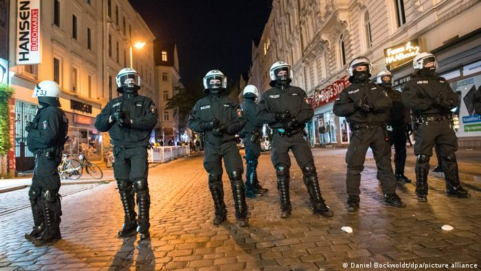 police stand across a street in the Schanzenviertel at night