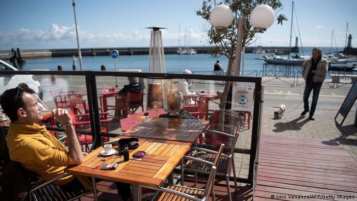 Homem sentado em uma mesa externa de um café. Sobre a mesa está uma xícara de café. Há uma barreira de vidro na frente dele. Ao fundo está o mar.