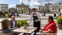 BERLIN, GERMANY - MAY 21: People sit outside at a restaurant near Brandenburg Gate for the first time this year during the coronavirus pandemic on May 21, 2021 in Berlin, Germany. Authorities are easing lockdown measures across Germany, enabling restaurants to offer outdoor service, hotels to accommodate tourists, cultural institutions to perform and other activities to resume. Covid infection rates have been falling consistently and the national average is now below 80 per 100,000 over a seven-day period. Meanwhile the pace of vaccinations is still climbing, with approximately 40% of the population having received a first dose. (Photo by Maja Hitij/Getty Images)