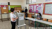 A Cypriot woman casts her ballot at a polling station in the capital Nicosia during voting on May 30, 2021 in parliamentary elections amid simmering public anger over the golden passports corruption scandal on the Mediterranean island. - Ultra-nationalists looking to exploit the anti-establishment mood have also played on concerns over migration, another hot-button issue for the European Union's most easterly member state. (Photo by Iakovos Hatzistavrou / AFP)