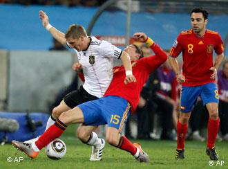 Spain's Sergio Busquets, left, challenges Germany's Lukas Podolski