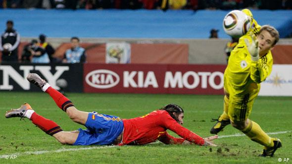 Spain's Sergio Ramos, left, tries to score a goal past Germany goalkeeper Manuel Neuer, right.