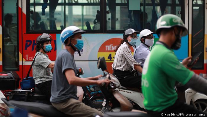 People wearing facemasks on motorbikes in Hanoi