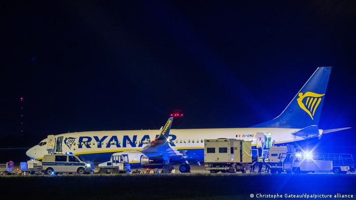 The Ryanair plane on the runway surrounded by police vans with blue lights on